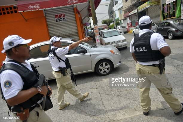 Police officers patrol a street of Acapulco Guerrero state Mexico on July 7 2017 after some detonations where heard near the place where the funeral...