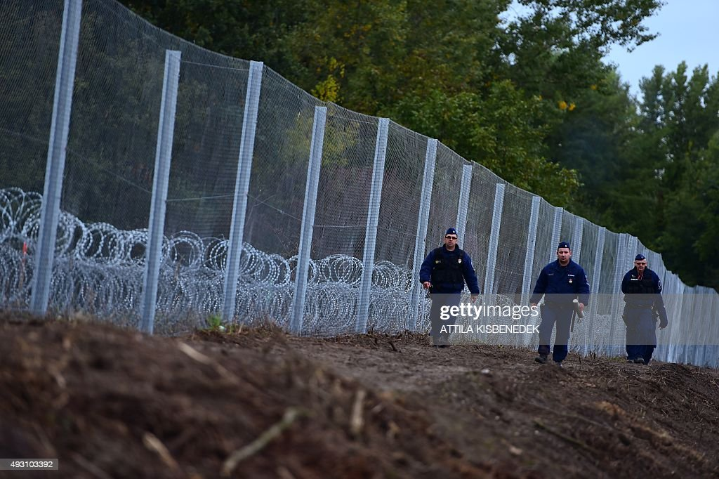Police officers patrol along a new border fence at the HungarianCroatian border near Zakany on October 17 2015 The border between Hungary and Croatia...