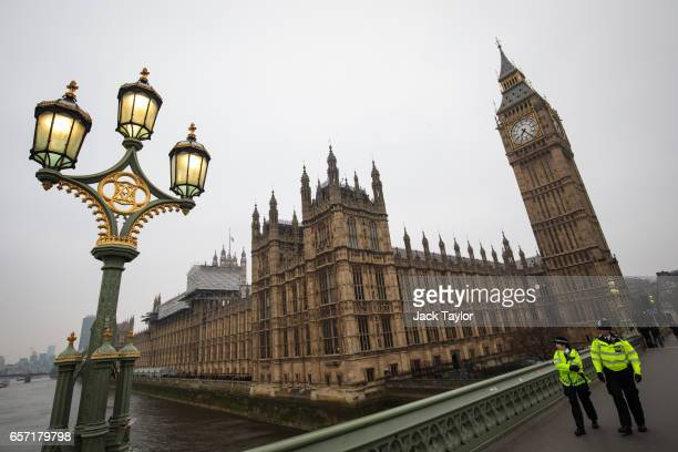 Police officers patrol along Westminster Bridge by the Houses of Parliament after the bridge was reopened following Wednesday's attack on Westminster...