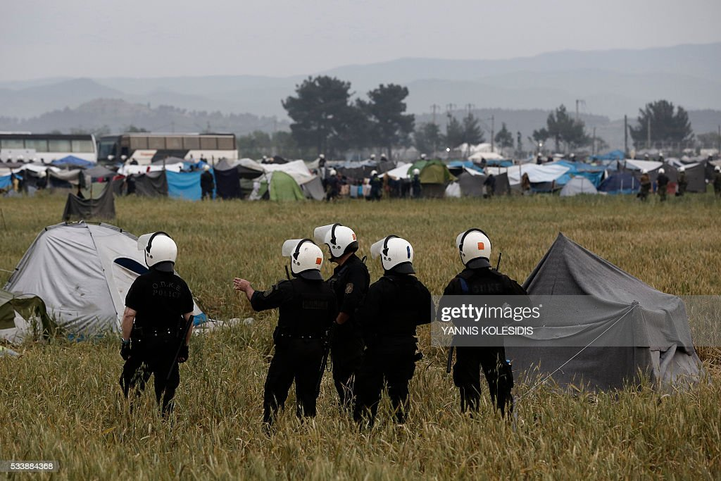 Police officers patrol among tents during an evacuation operation by police forces of a makeshift migrant camp at the border at the Greek-Macedonian border near the village of Idomeni, on May 24, 2016. In an operation which began shortly after sunrise on May 24, hundreds of Greek police began evacuating the sprawling camp which is currently home to 8,400 refugees and migrants, among them many families with children, an AFP correspondent said. At its height, there were more than 12,000 people crammed into the site, many of them fleeing war, persecution and poverty in the Middle East and Asia, with the camp exploding in size since Balkan states began closing their borders in mid February in a bid to stem the human tide seeking passage to northern Europe. / AFP / POOL / YANNIS