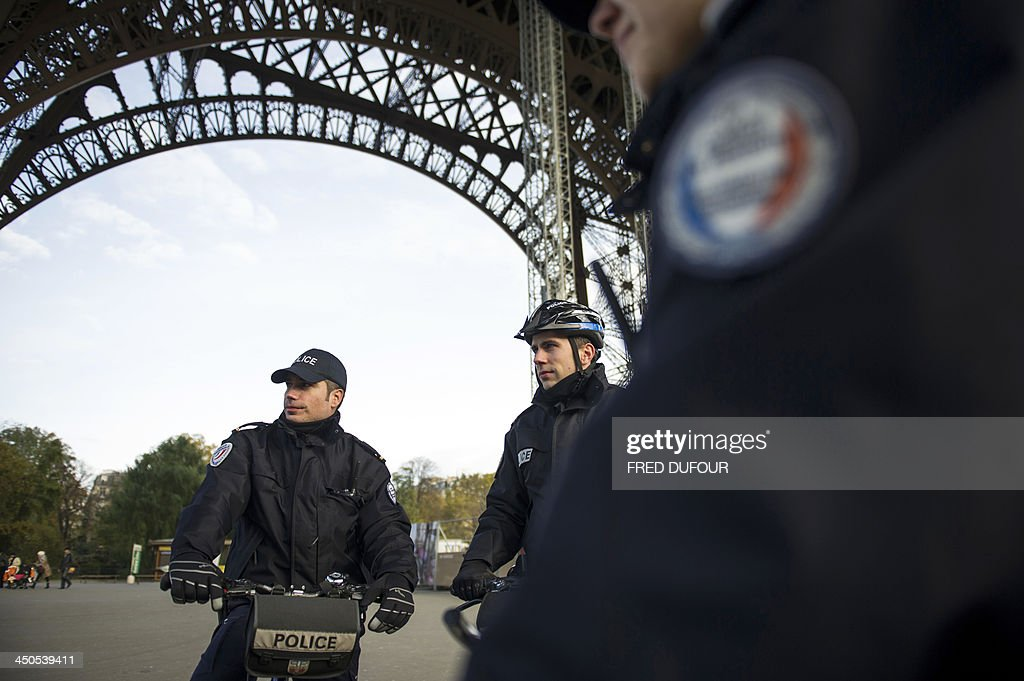 Police officers patrol around the Eiffel tower on November 19, 2013 in Paris as a manhunt is under way in the capital for a lone gunman who shot and critically wounded a newspaper photographer in his office on November 18 before opening fire outside a bank headquarters and hijacking a car. Officers on foot and in squad cars fanned across the nervous city, taking up positions outside media offices, along the Champs-Elysees avenue and at entrances to underground train stations. Investigators have so far been unable to identify the gunman, described by French Interior Minister Manuel Valls as 'a real danger'.