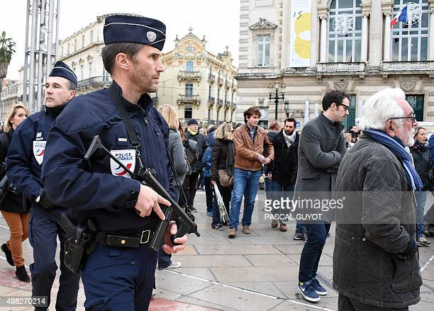 Police officers patrol as people take part in a peace march in central Montpellier on November 22 2015 to pay tribute to the victims of the November...