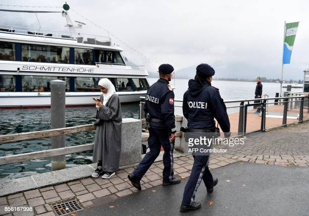 Police officers patrol as they pass by a woman wearing a traditonal hijab headdress in Zell am See Austria on October 1 2017 Austria's ban on...