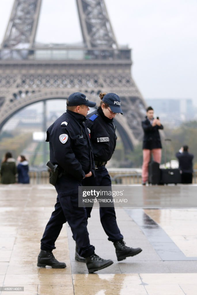 Police officers patrol at the Trocadero Esplanade (also named Human rights Esplanade) in front of the Eiffel Tower in Paris on November 19, 2013 as a manhunt is under way in Paris for a lone gunman who shot and critically wounded a newspaper photographer in his office on November 18 before opening fire outside a bank headquarters and hijacking a car. Officers on foot and in squad cars fanned across the nervous city, taking up positions outside media offices, along the Champs-Elysees avenue and at entrances to underground train stations. Investigators have so far been unable to identify the gunman, described by French Interior Minister Manuel Valls as 'a real danger'.