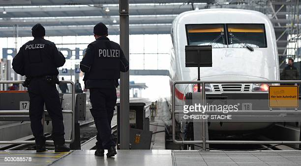 Police officers patrol in front of a train in front of a train at the main train station in Munich southern Germany on January 1 2016 German police...