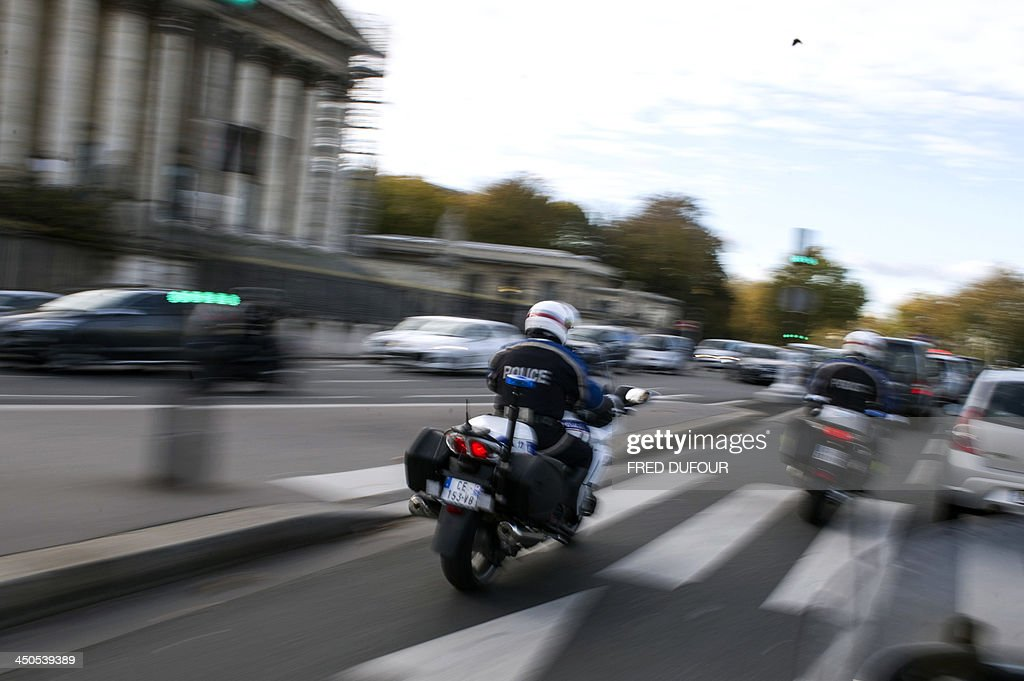 Police officers patrol in the streets of Paris on November 19, 2013 as a manhunt is under way in the city for a lone gunman who shot and critically wounded a newspaper photographer in his office on November 18 before opening fire outside a bank headquarters and hijacking a car. Officers on foot and in squad cars fanned across the nervous city, taking up positions outside media offices, along the Champs-Elysees avenue and at entrances to underground train stations. Investigators have so far been unable to identify the gunman, described by French Interior Minister Manuel Valls as 'a real danger'.