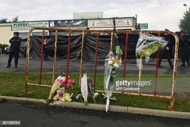 Police officers patrol next to a makeshift memorial in front of the scene of a car crash into a pizza restaurant on August 15 2017 in SeptSorts 55km...