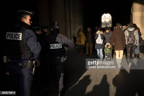 Police officers patrol outside the Louvre Museum in Paris on December 30 2016 / AFP / LIONEL BONAVENTURE