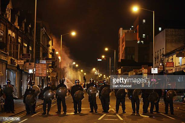 Police officers patrol the streets as a large fire engulfs shops and residential properties in Croydon on August 9 2011 in London England Sporadic...