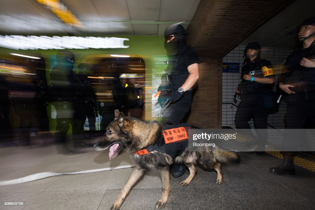 Police officers patrol with a security dog during an anti-terror drill on the sidelines of the Ulchi Freedom Guardian (UFG) military exercises at a subway station in Seoul, South Korea, on Tuesday, Aug. 22, 2017. North Korea warned the U.S. on Tuesday it will face 'merciless revenge' for ignoring Pyongyangs warnings over annual military drills with South Korea. Photographer: SeongJoon Cho/Bloomberg via Getty Images