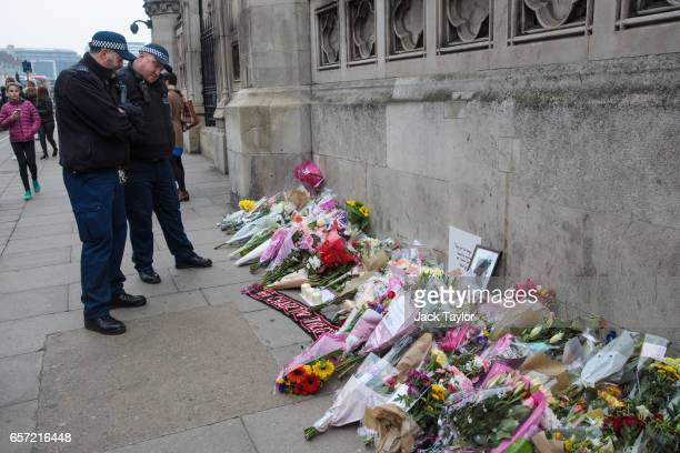 Police officers pause in front of floral tributes laid outside the Houses of Parliament following Wednesday's attack on Westminster on March 24 2017...