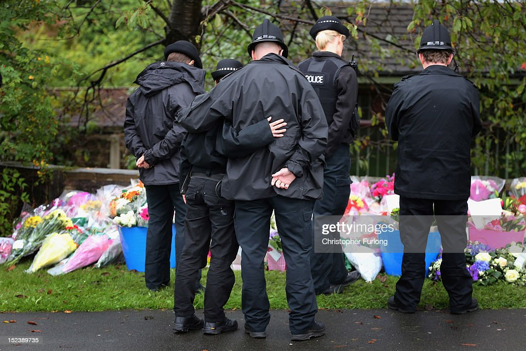 Police officers pay their respects after laying flowers near to the scene of the shooting of WPCs Nicola Hughes and Fiona Bone in Hattersley on September 20, 2012 in Manchester, England. Local man Dale Cregan, 29, has been arrested in connection with the shooting of WPC's Nicola Hughes and Fiona Bone, who suffered fatal injuries in a gun and grenade attack in Mottram, during a routine call to investigate a burglary in Abbey Gardens on Tuesday.