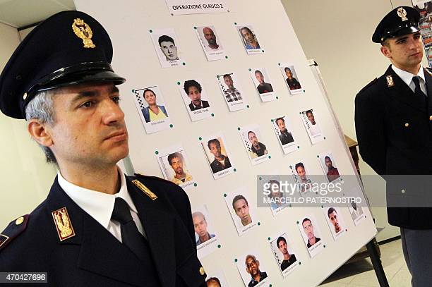 Police officers pose next to pictures of 24 alleged human traffickers released by Italian police during a press conference in Palermo on April 20...