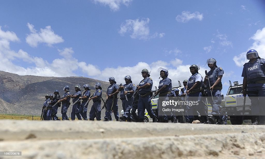 Police officers prepare for protestors at the N1 De Doorns protest on January 9, 2013, in Cape Town, South Africa. The farm workers' protest for R150 a day wages turned violent and the authoroties had to step in.