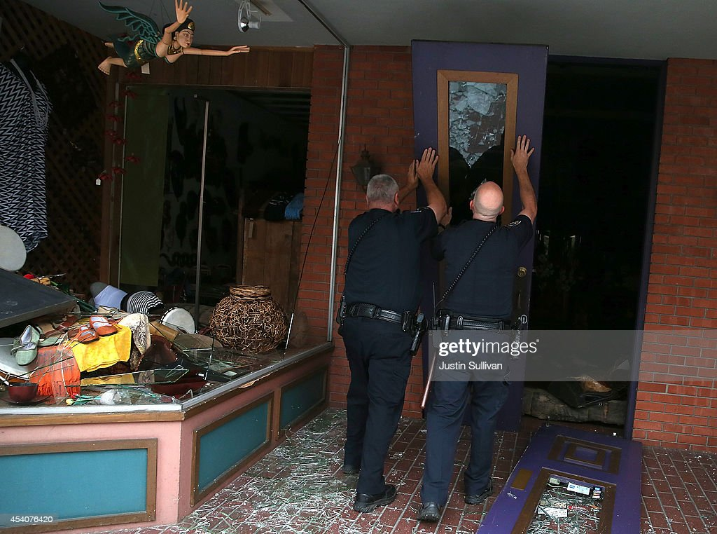 Police officers prop up a fallen door in front of a damaged buillding following a reported 6.0 earthquake on August 24, 2014 in Napa, California. A 6.0 earthquake rocked the San Francisco Bay Area shortly after 3:00 am on Sunday morning causing damage to buildings and sending at least 70 people to a hospital with non-life threatening injuries.
