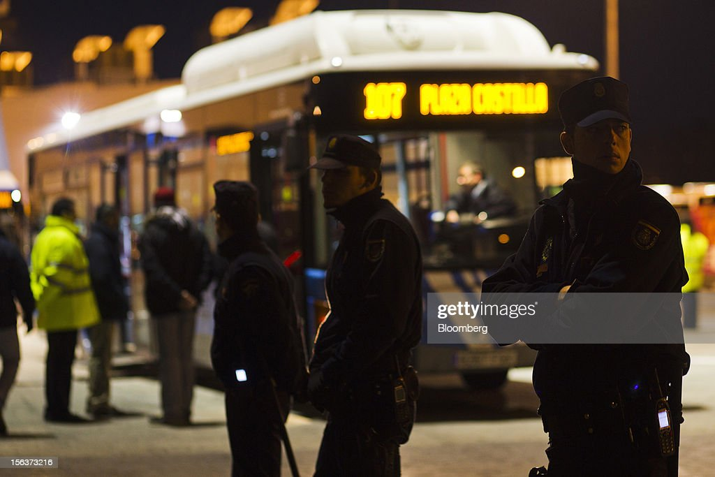 Police officers protect buses as they leave the Empresa Municipal de Transportes de Madrid (EMT) depot on the morning of a general strike in Madrid, Spain, on Wednesday, Nov. 14, 2012. Spanish unions today staged their second general strike against Prime Minister Mariano Rajoy as mounting opposition to budget cuts and bank bailouts undermines the 11-month-old government's ability to repair the economy. Photographer: Angel Navarrete/Bloomberg via Getty Images
