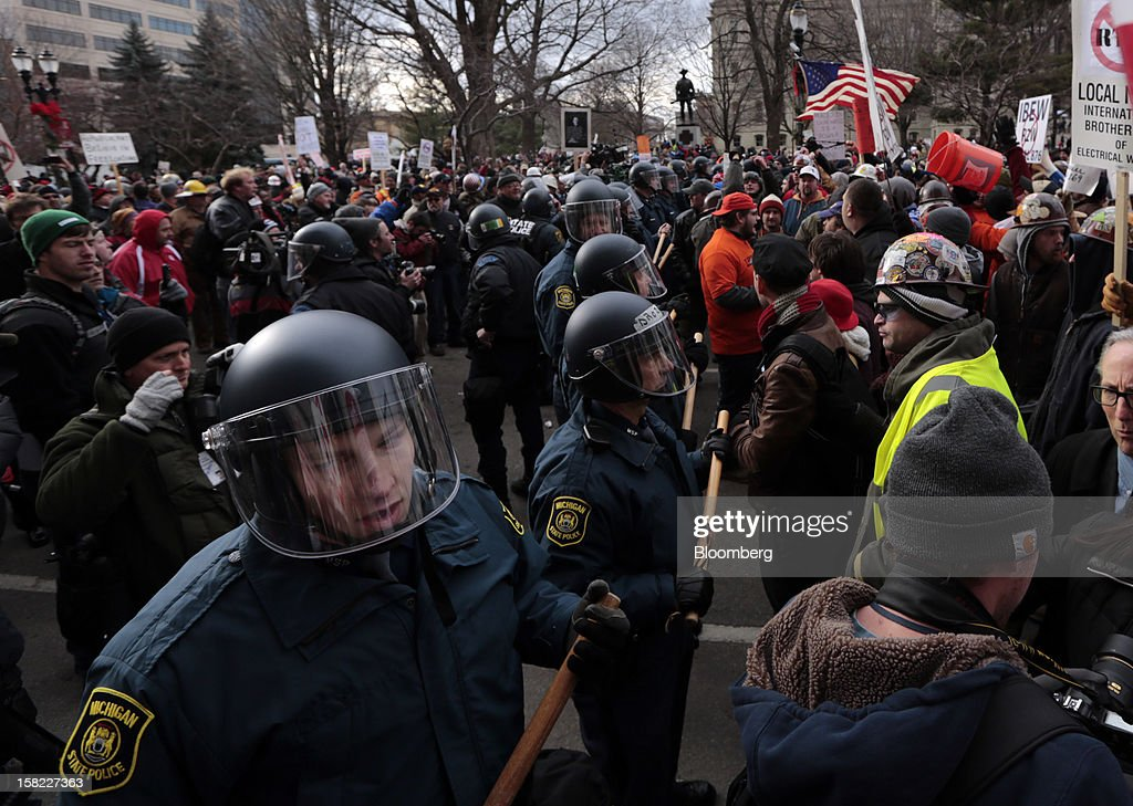 Police officers protect the George W. Romney state office building as protesters hold a sit-in during a demonstration in Lansing, Michigan, U.S., on Tuesday, Dec. 11, 2012. Michigan lawmakers approved bills to prohibit mandatory union dues in workplaces as thousands of chanting protesters thronged the Capitol. Photographer: Jeff Kowalsky/Bloomberg via Getty Images