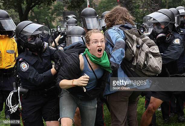 Police officers push back and use their battons to strike demonstrators protesting the G8/G20 summits on June 26 2010 in Toronto Ontario Canada Store...