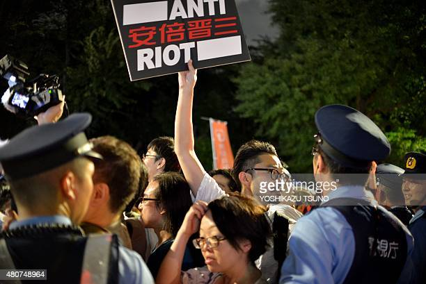 Police officers push back demonstrators as civic group members staged an antigovernment rally outside the National Diet in Tokyo on July 15 2015 to...