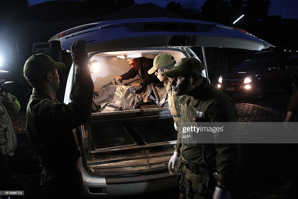 Police officers put a corpse into a car as they work at the site of an accident apparently caused when a bus driver lost control of the vehicle in Tome, in Biobio province, some 500 km south of Santiago, on February 9,2013. At least 15 people were killed and 19 others were injured when the bus full of passengers fell into a ravine in central Chile, a local official said.