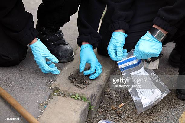 Police officers put possible evidence in a bag near the property of a man arrested on suspicion of murder on May 27 2010 in Bradford England West...