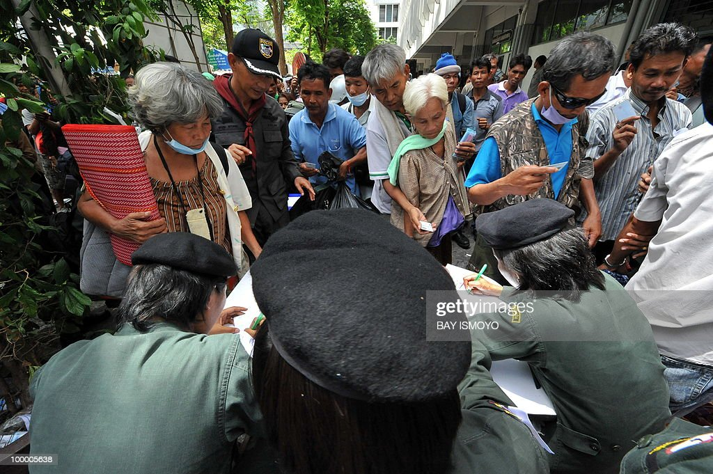 Police officers register the names of 'Red Shirt' anti-government protestors as they leave the police headquarters before boarding buses out of their dismantled protest site a day after an army assault, in downtown Bangkok on May 20, 2010. Plumes of smoke hung over the Thai capital and gunfire crackled As troops moved to crush militants who went on the rampage after a deadly crackdown on their anti-government protest camp.