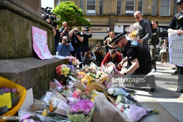 Police officers relocate floral tributes in St Ann's Square in Manchester northwest England on May 23 laid as a mark of respect to those in killed...
