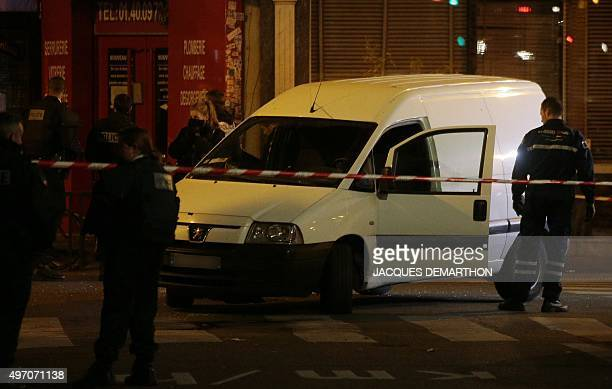 Police officers remove a car that was abandoned by passerby during an attack outside the La Belle Equipe cafe rue de Charonne on November 14 2015 in...