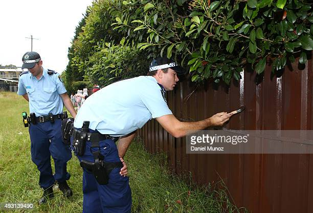 Police officers remove a graffiti during Graffiti Removal Day at Werrington on October 18 2015 in Sydney Australia