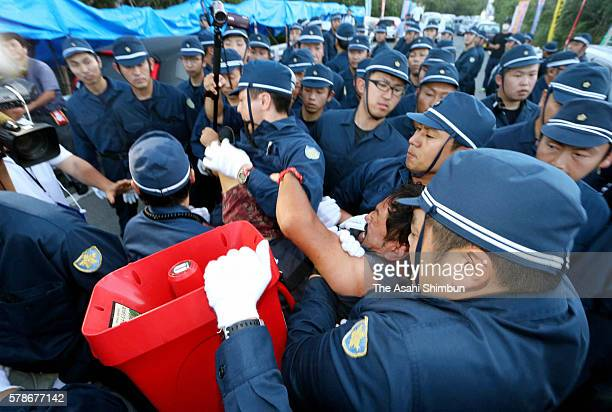Police officers remove a sitin protester against the relocation of the US helipads in preparation for resuming the construction on July 22 2016 in...