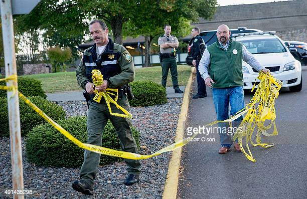 Police officers remove crime scene tape on the campus of Umpqua Community College as it reopens on October 5 2015 in Roseburg Oregon The campus was...
