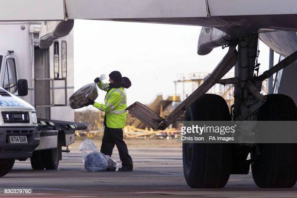 Police officers remove evidence from the hijacked Afghan Ariana 727 plane as it sits on the tarmac at Stansted Airport in Essex after the hijackers...