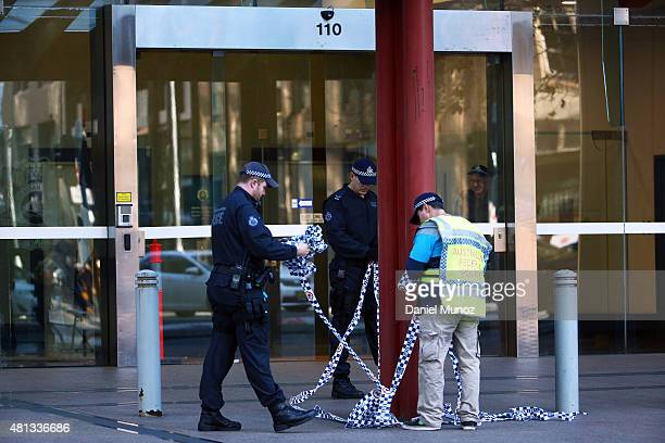 Police officers remove police tape from the entrance of the Australian Federal Police headquarters after removing a suspicious package on July 20...