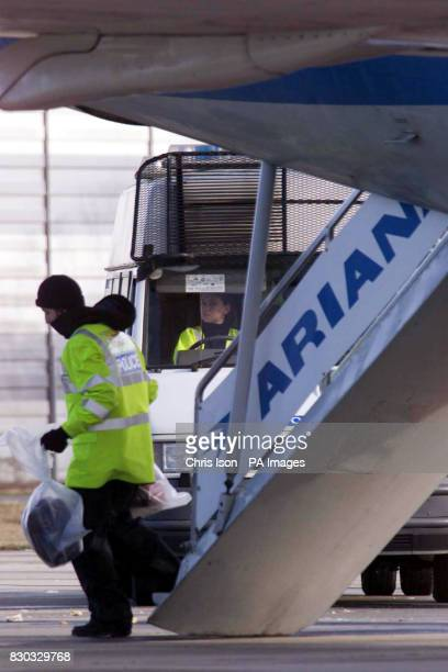 Police officers remove potential evidence from the hijacked Afghan Ariana 727 plane as it sits on the tarmac at Stansted Airport in Essex after the...