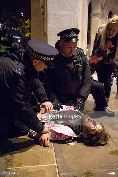 Police officers restrain a protester during the Million Mask March on November 5 2016 in London England Thousands of demonstrators many wearing the...