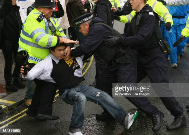 Police officers restrain a protester during the relay of the Olmypic torch during its journey across London on its way to the lighting of the Olympic...
