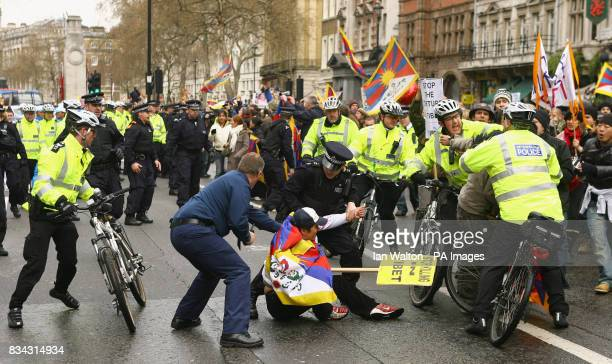 Police officers restrain a protester during the relay of the Olympic torch during its journey across London on its way to the lighting of the Olympic...
