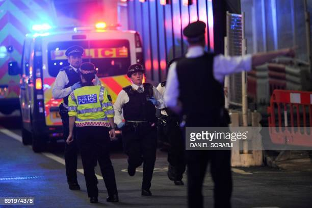 Police officers run at the scene of an apparent terror attack on London Bridge in central London on June 3 2017 Armed police fired shots after...