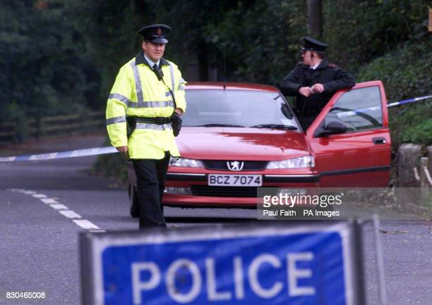 Police officers seal off the road near the scene of a booby trap explosion at a railway track near Larne in Co Antrim Northern Ireland One man...