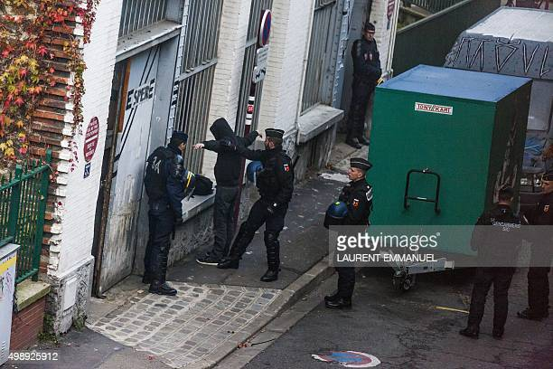 Police officers search a man during a Police and Gendarmerie raid in a building believed to be squatted in Le Pre SaintGervais northeast of Paris on...