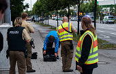Police officers search a man outside the shopping center as they respond to a shooting at the Olympia Einkaufzentrum at July 22 2016 in Munich...