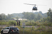 Police officers search an area for suspects involved in shooting an officer September 1 2015 in Fox Lake Illinois A manhunt for three suspects is...
