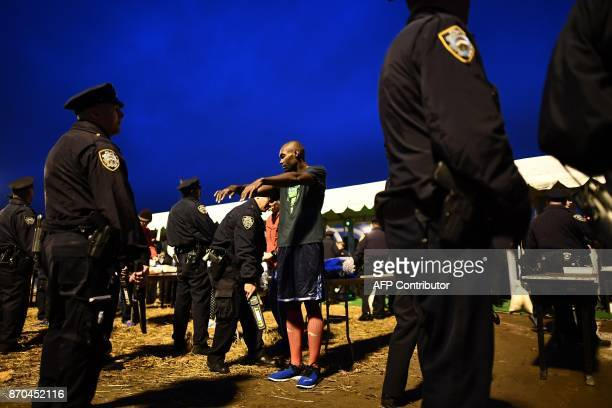 Police officers search athletes at a checkpoint as they arrive for the New York City Marathon in New York on November 5 2017 Five days after the...