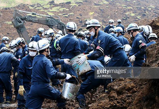 TOPSHOT Police officers search for missing victims in the village of MinamiAso Kumamoto prefecture on April 19 2016 Two major earthquakes and about...