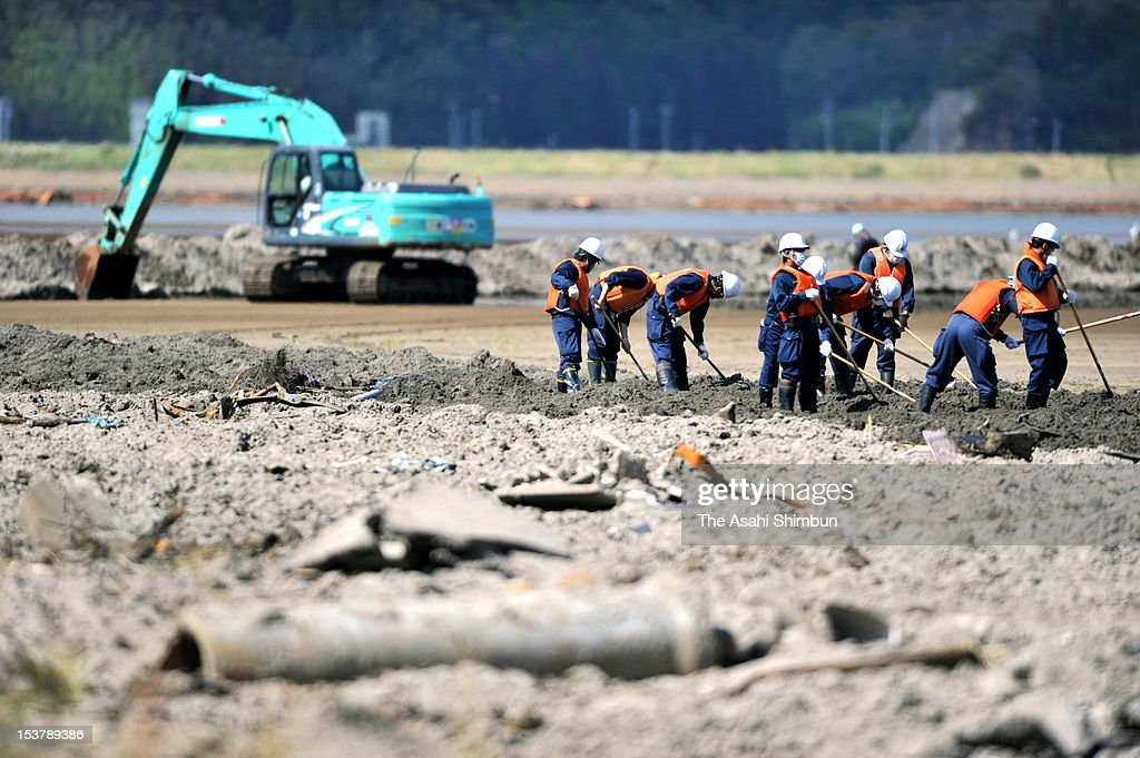 Police officers search missings at the Nagatsura area, on October 8, 2012 in Ishinomaki, Miyagi, Japan. The 224 hectare area, had sunk under the seawater by the March 11 earthquake and tsunami causing 80-centimeter land subsidence, was thought to be the final untouched ground for search missings. Okawa Elementary School, where 70 out of 108 pupils were killed by the earthquake triggered tsunami, used to be located the upstream site and still 38 including 4 pupils are missing in this area.