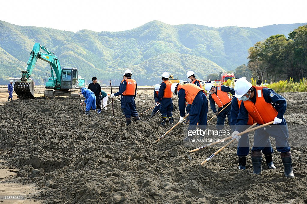 Police officers search missings at the Nagatsura area, on October 8, 2012 in Ishinomaki, Miyagi, Japan. The 224 hectare area, had sunk under the seawater by the March 11 earthquake and tsunami causing 80-centimeter land subsidence, was thought to be the final untouched ground for search missings. Okawa Elementary School, where 70 out of 108 pupils were killed by the earthquake triggered tsunami, used to be located the upstream site and still 38 including 4 pupils are missing.