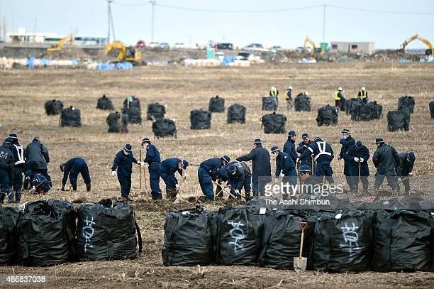 Police officers search missings or any remains of vicitms while bags of contaminated soil are placed on the field on the fourth anniversary of the...