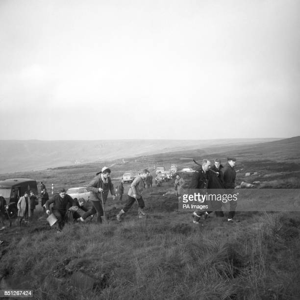 Police officers search Saddleworth Moor near Woodhead with spades and shovels as they look for hidden graves after reports bodies may be in them At...