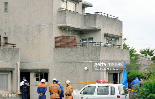 Police officers search the area around the burnedout apartment room in a prefecturerun apartment complex on October 6 2017 in Hitachi Ibaraki Japan...