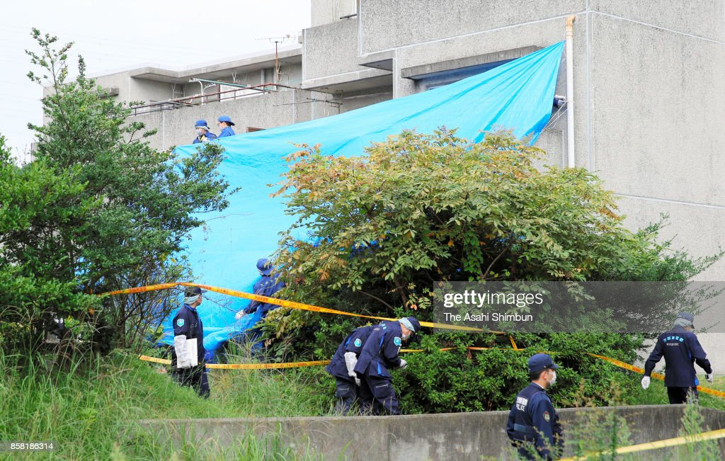 Police officers search the area around the burned-out apartment room in a prefecture-run apartment complex on October 6, 2017 in Hitachi, Ibaraki, Japan. The bodies of a woman and four boys were discovered in a burned-out apartment room after a man told police he had set his home on fire. Hirobumi Komatsu, 32, also told police he had stabbed his family members, investigative sources said. According to police, the six victims are believed to be the suspect's 33-year-old wife; his daughter, 11, an elementary school sixth-grader; his oldest son, 7; second son, 5; and 3-year-old twin sons.